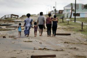The Emberton family walk through debris along highway A1A in Flagler Beach, Florida.