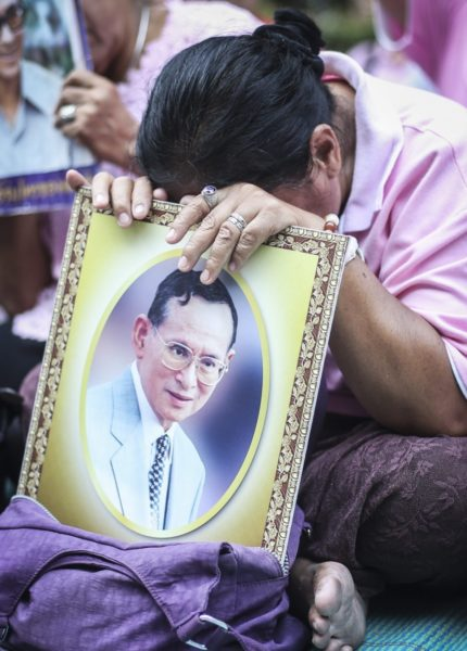 A Thai well-wisher weeps as she prays for the Thai King before his death.