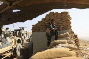An Iraqi Kurdish Peshmerga fighter stands guard about 15 kilometres from Mosul's outskirts.