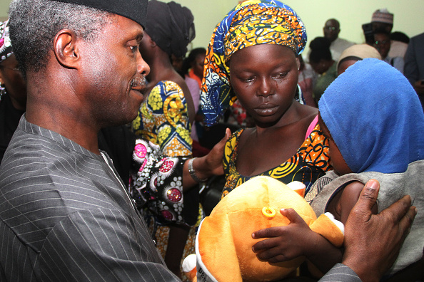 One of the 21 freed Chibok girls cries while holding her baby. Photo: Getty