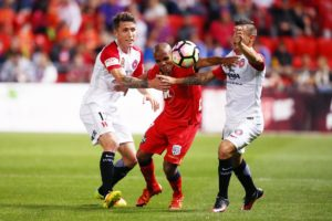 Adelaide's Henrique gets some attention from two Wanderers opponents.