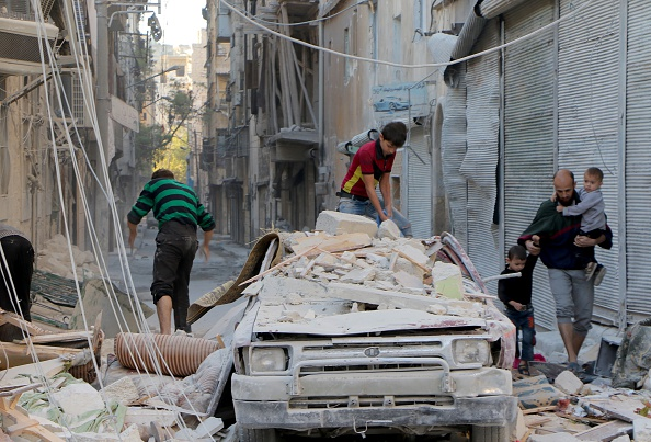 Syrians inspect the debris of collapsed buildings. Photo: Getty