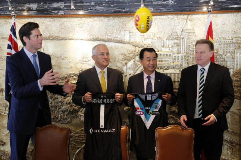 Australian Prime Minister Malcolm Turnbull, second from left, watches the ball flying past David Koch, right, chairman of Port Adelaide Football Club, and Gui Guojie, general manager of Shanghai CRED Real Estate Stock, second from right, as Gillion McLachlan, CEO of Australia Football League, prepares to catch it after a signing of the memorandum of understanding at a hotel in Shanghai, China, Thursday, April 14, 2016.