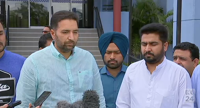 The brother of the Brisbane bus driver who was killed, Amit Alisher (R) says the attack was racially motivated.