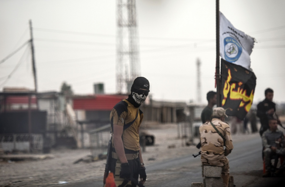 An Iraqi soldier in a skull mask waits at a checkpoint for people fleeing the city of Mosul. Photo: Getty