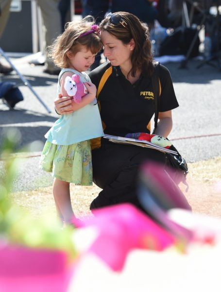 A mother and her young daughter pay their respects to the four victims at Dreamworld.