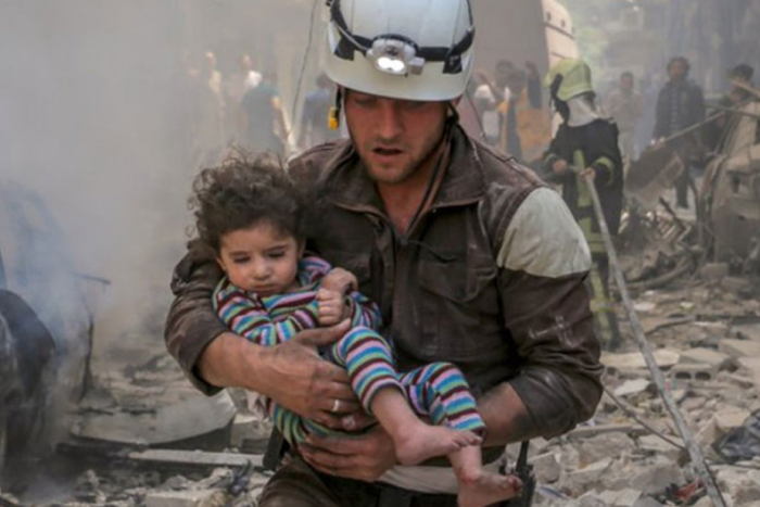 A member of Syria Civil Defence carries a child amid a ruined building Photo: ABC