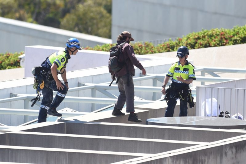 A police officer escorts a pro refugee protester who abseiled from the roof of Parliament House in Canberra.