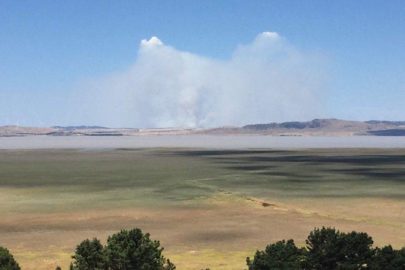 Plumes of smoke rise from beyond Lake George.