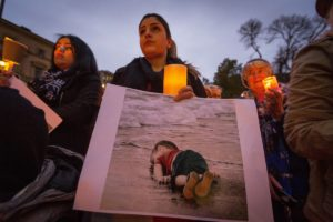 A woman holds a picture of Aylan Kurdi during a 2015 remembrance vigil in Melbourne.