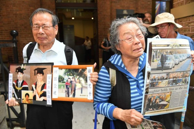 Lin family grandparents Feng Qing Zhu and Yang Fei Lin, with photos of their murdered grandchildren, wept outside court.