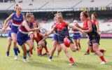 Daisy Pearce kicks downfield during a 2015 AFLW exhibition match.