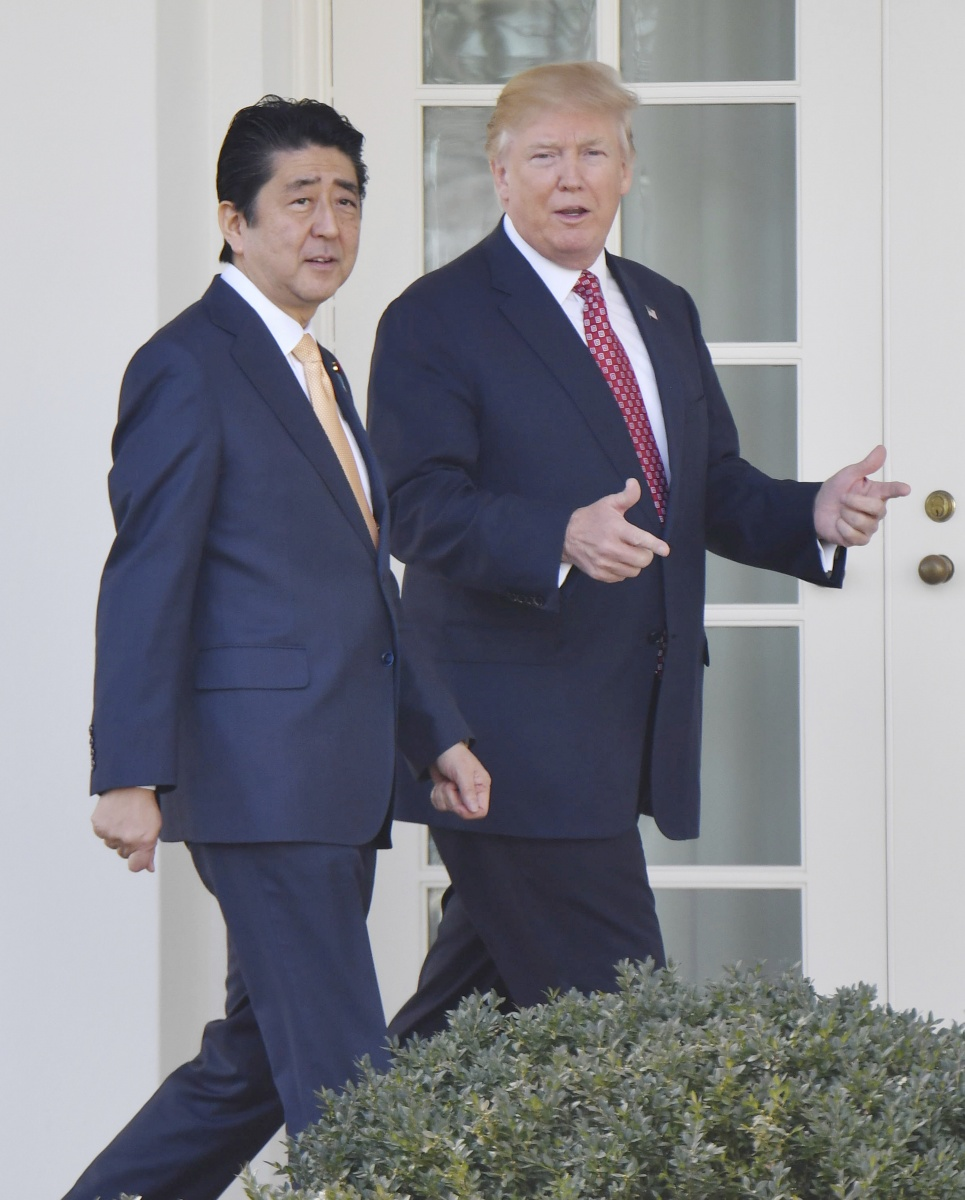 US President Trump walks with PM Shinzo Abe on their way to White House press conference. Photo: AAP