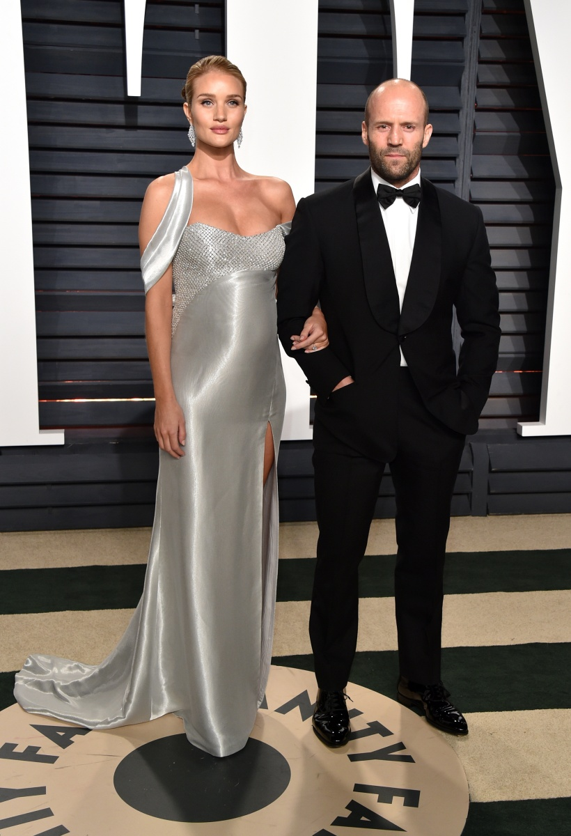 Pregnant supermodel Rosie Huntington-Whiteley shimmers in silver alongside her dapper fiance Jason Statham.