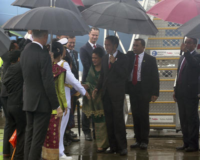 Indonesian President Joko Widodo and his wife Iriana are met by officials in a wet Sydney. Photo: AAP