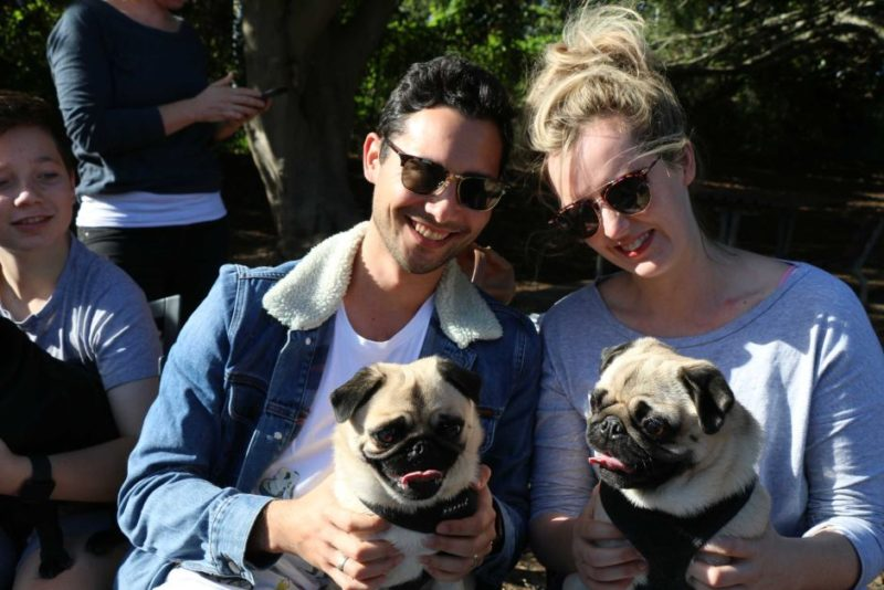 Alex and Emma pose with their pugs