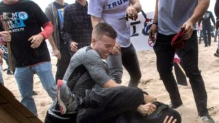 A Trump supporter beats an anti-Trump protester during wild scenes in Huntington Beach, Calif.