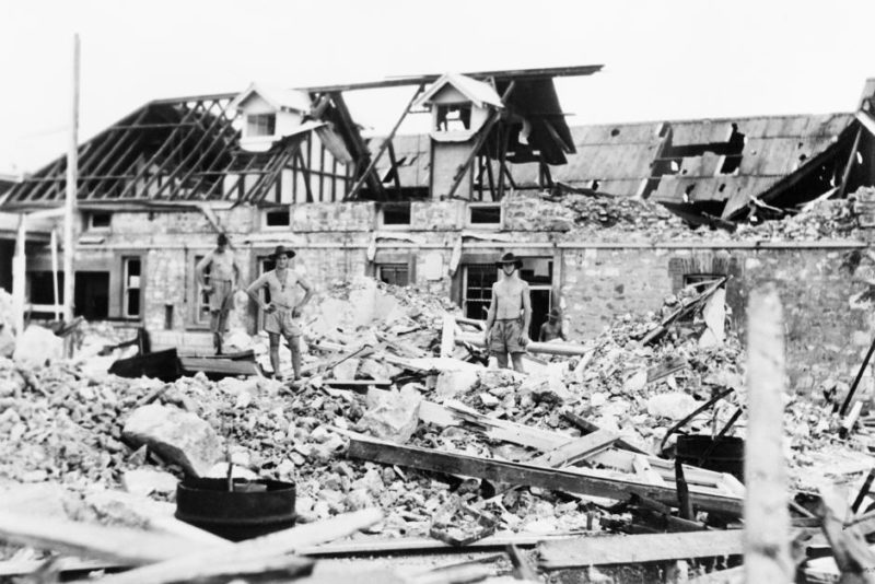 Australian troops inspect bomb damage caused by air raids