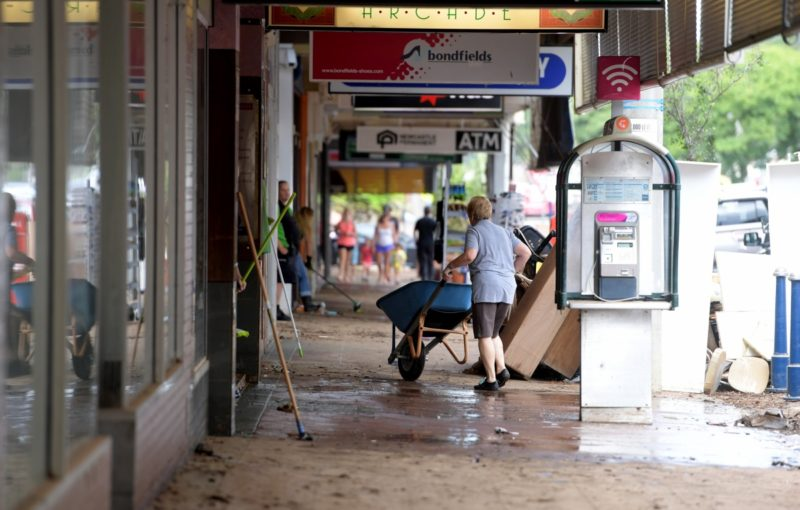 Locals clean debris in the centre town centre as floodwater recedes after the levee broke inundating Lismore