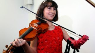 Isabella Cabrera beams with delight as she plays her violin for the first time with her new robotic arm.