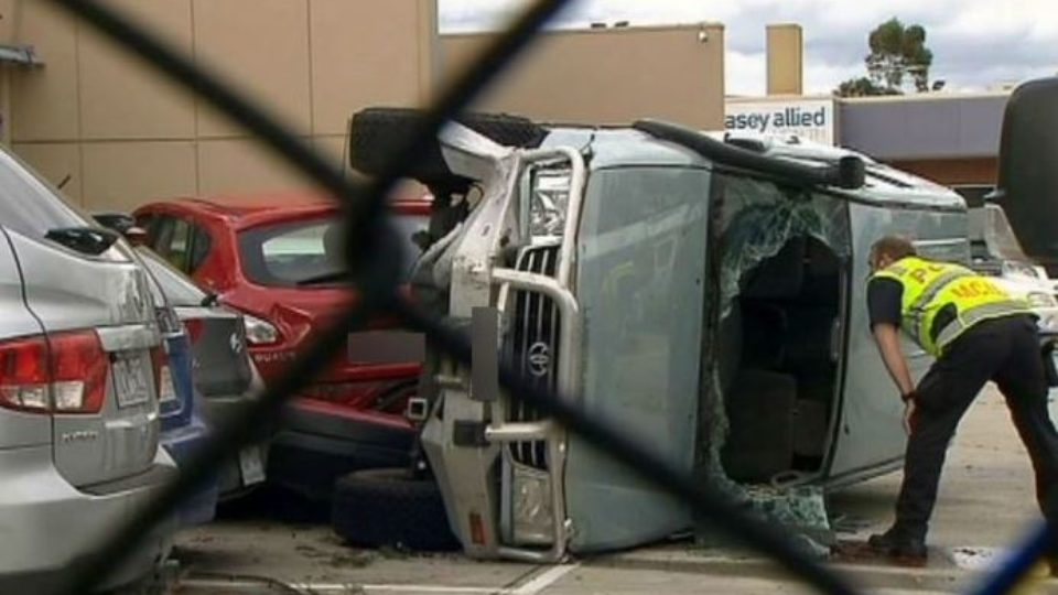 A police officer peers into the overturned Land Cruiser after Brax Kyle was killed in a Melbourne carpark on Friday.