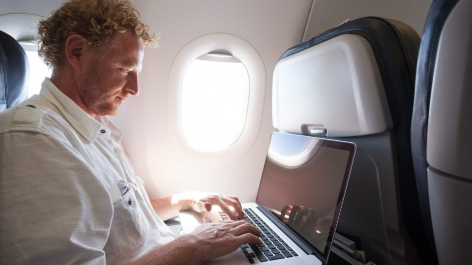 man using laptop on plane
