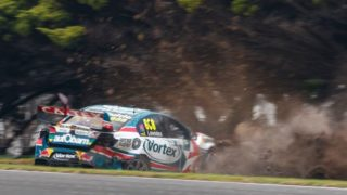 Craig Lowndes' battered Commodore slides to a halt in a cloud of dust at the Phillip Island Grand Prix Circuit.