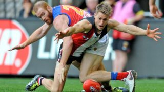 The Saints tenacious Sean Dempster on the receiving end of a hard tackle by Sean Dempster of the Saints is tackled by the Lions' Daniel Merrett late in the 2016 season.