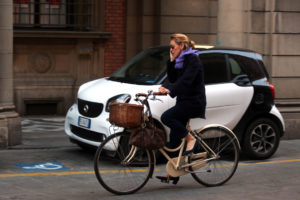 A woman talks on her mobile phone while cycling in Bologna, Italy