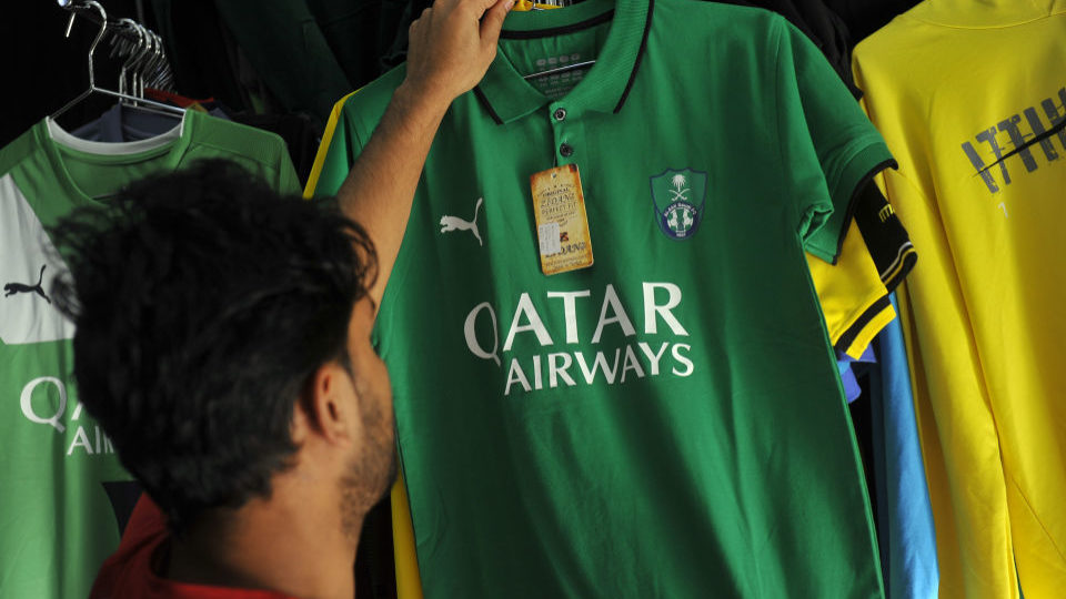A man looks at a shirt of Saudi Arabia's Al-Ahli Football Club bearing a Qatar Airways' logo in the city of Jeddah on Tuesday