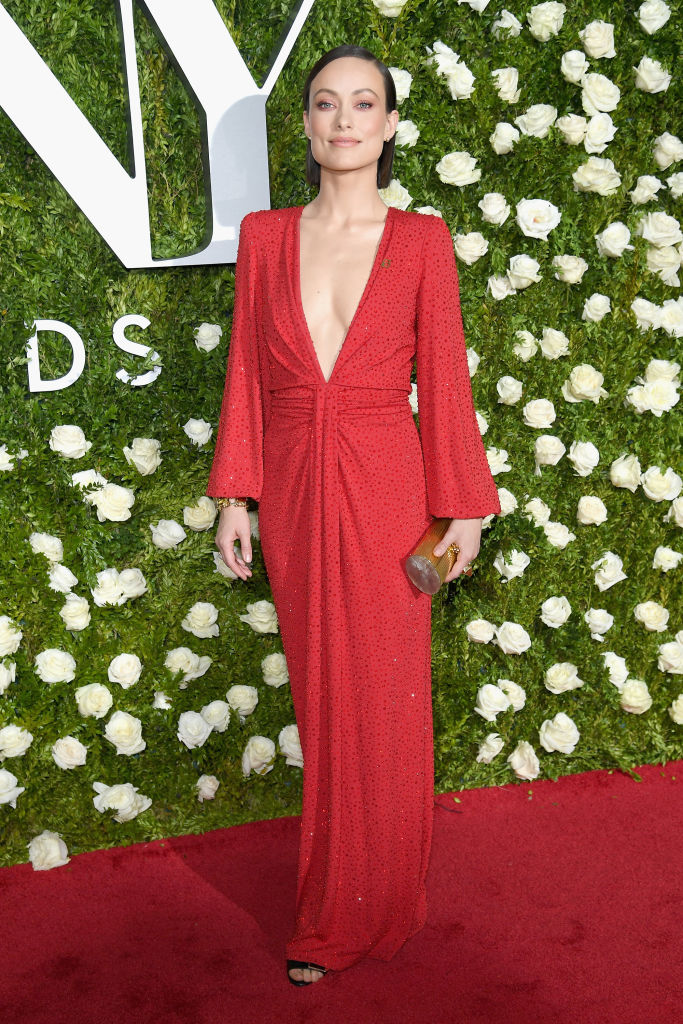 Olivia Wilde wears a detailed red dress with plunging neckline.