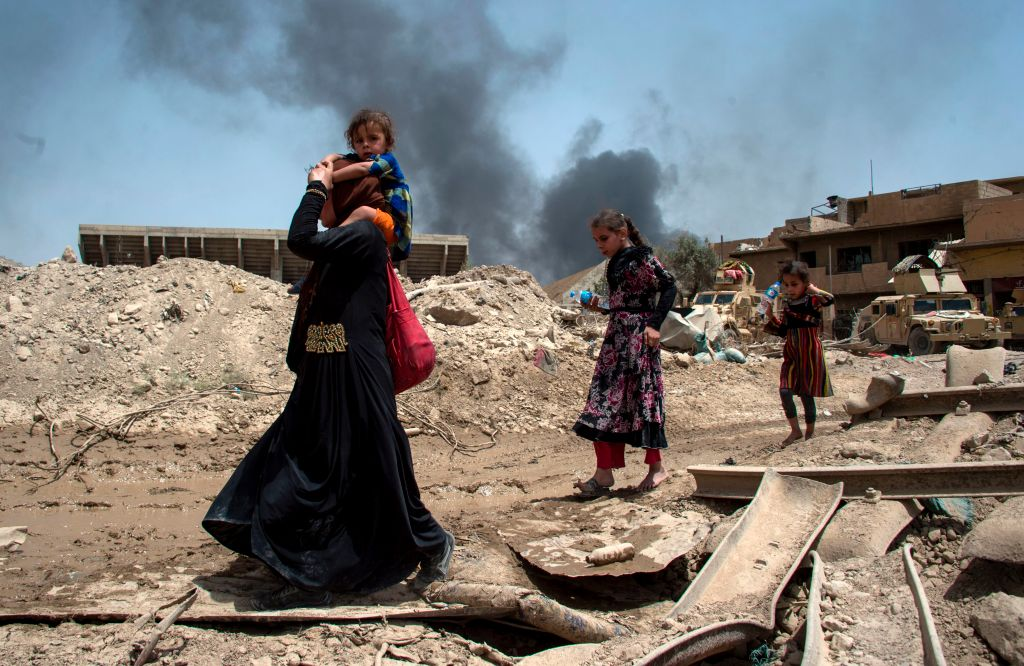 An Iraqi woman and children flee the Old City of Mosul on July 3 as Iraqi-forces closed in on Islamic State fighters