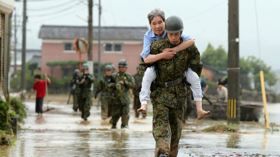 Japanese soldiers help local residents evacuate from floods in Fukuoka on Thursday