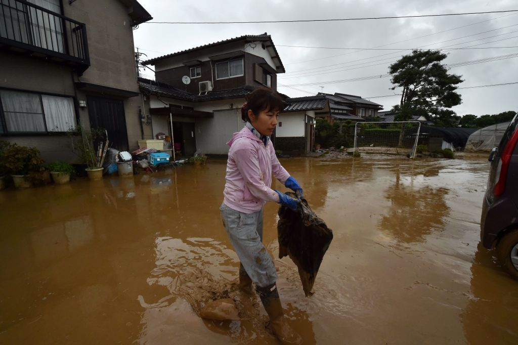 A local resident takes out flood-damaged belongings from her house in Fukuoka on Thursday