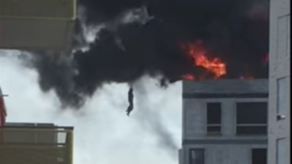 A roofer has been lowered to safety from a burning building by grabbing onto a crane hook
