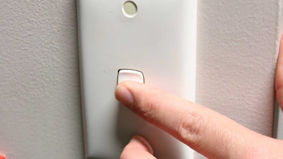 A hand turns on a light switch