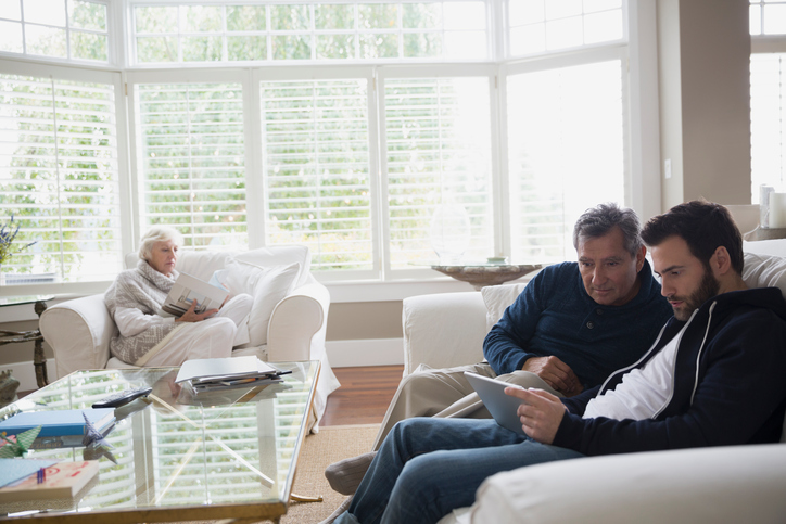 Father and son using digital tablet living room sofa