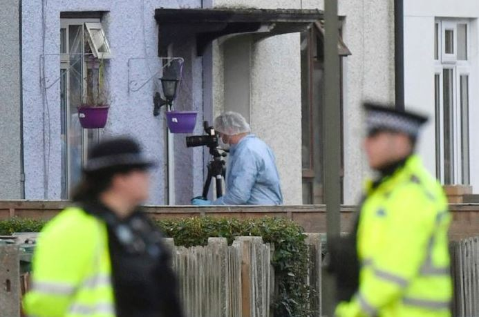 A police forensic specialist investigates the London home where the suspect is believed to have lived