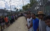 Refugees and asylum seekers are pictured lined up together at the Manus Island detention centre as they resist being forced out.