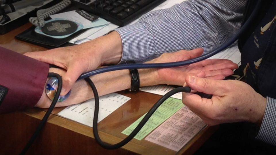 Close up of doctor taking patient's pulse using stethoscope