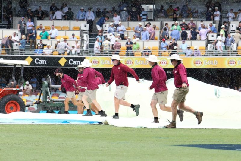 Ground staff rush to cover the pitch at the Gabba