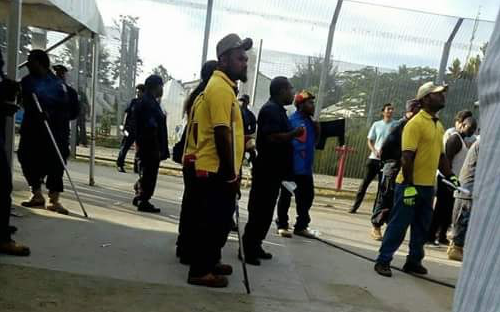 PNG police are pictured at the Lombrum site on Thursday with what appears to be makeshift batons.