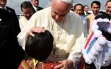 Pope Francis is greeted by a child upon his arrival at Yangon International Airport in Myanmar.