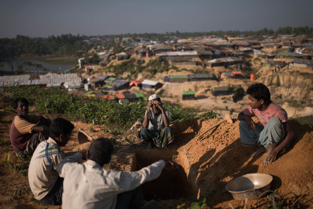 Rohingya Muslim refugee grave-diggers wait to bury the body of an elderly woman who died from an un-diagnosed illness on a hillside in the Kutupalong refugee camp.