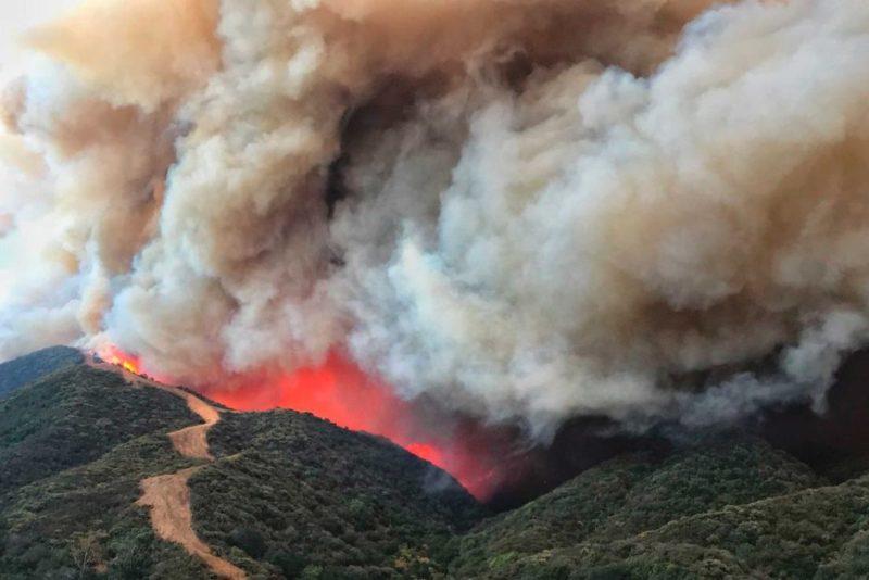 Flames advance towards a fire break in California