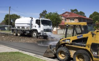 Industrial cleaners clear a Sydney street after eight tonnes of asbestos-contaminated waste was dumped.