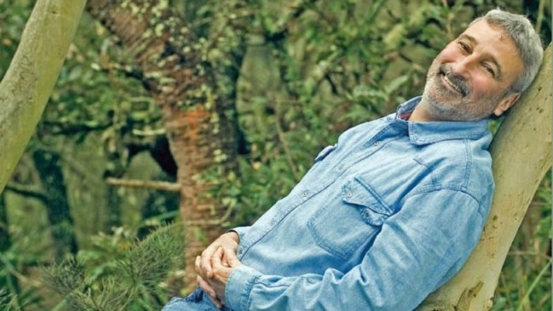 Don Burke reclining on a tree