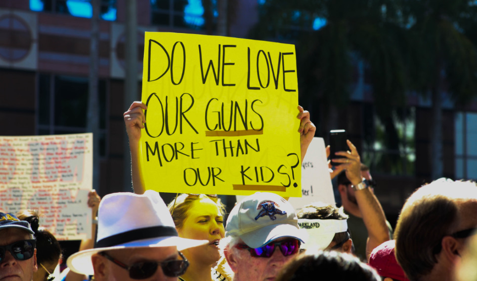 A protester raises the question motivating the latest push to end Americans' love affair with firearms