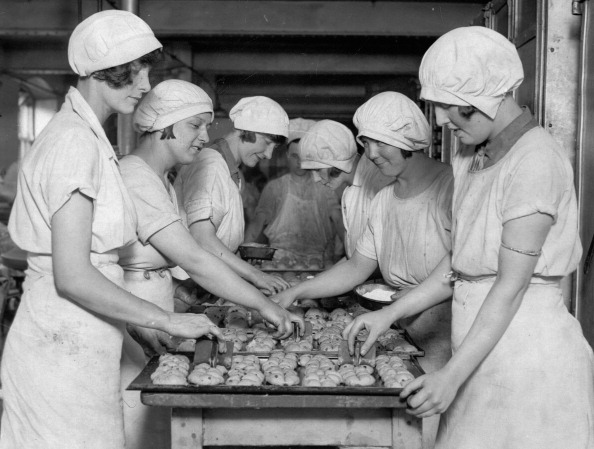 Young girls at a London bakery, stamping crosses on the hot cross buns for Easter in 1930.