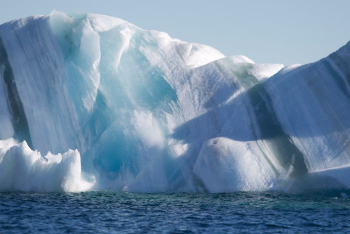 An iceberg showing dark stripes of marine ice and stripes of blue and white glacier ice and snow